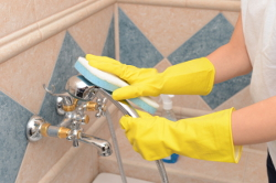 One-off Cleaner Scrubbing a Shower Tab
